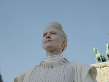 Worm's-eye view of the chest and face of a woman dressed in white with platinum blonde, short hair on a donkey, whose neck, cut at the left edge of the picture, is just visible. Background: Berlin Brandenburg Gate and steel blue sky