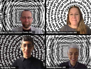 """Film still of a video conference. It shows as split screen four people, each sitting in front of a black and white background consisting of the lettering """"Abracadabra"""" in Latin and Hebrew letters arranged in concentric circles."""