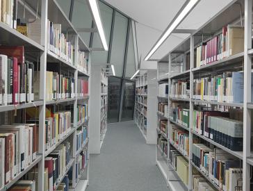 Blick in den Gang zwischen zwei Buchregalreihen in einer Bibliothek