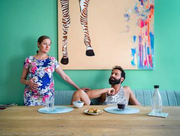 Fotografie einer hochschwangeren Frau im bunten Blumenkleid und eines jungen Mannes mit dunklem Bart an einem Esstisch, darauf drei Stücke Baklava, an der Wand hinter ihnen ein Gemälde mit Zebrabeinen