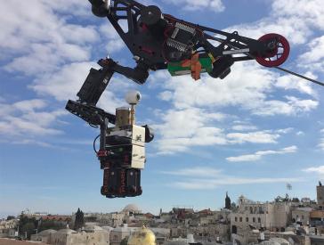 Eine an ein Stahlseil montierte Kamera schwebt vor blauem Himmel über die Dächer Jerusalems