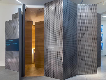 The debate room in the exhibition was realized as an eye-catching, jagged space within a space; its exterior is clad with perforated panels of metal, its interior with inviting-looking wood