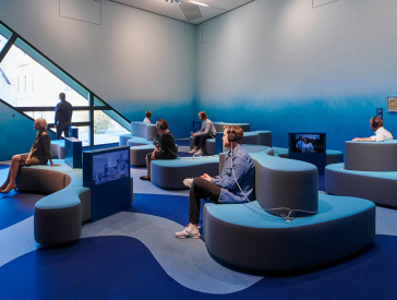 Room in shades of blue with undulating seating and recessed television screens
