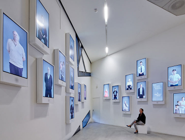 Exhibition space with numerous screens on the walls, each of which shows a person looking at the visitor.