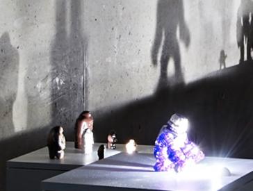 Ausstellungsansicht mit Actionfiguren, die Schatten an die Wand werfen