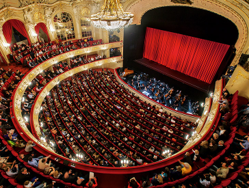 View into the hall of the Komische Oper with rows of chairs and visitors