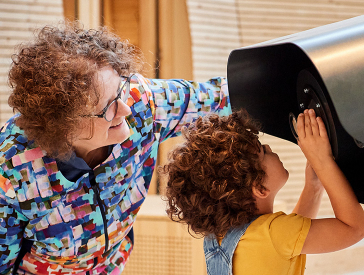 A woman and a child look through a telescope