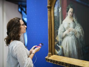 Junge Frau steht mit Smartphone und Kopfhörern vorm Porträt von Albertine Heine als Braut von August Theodor Kaselowsky