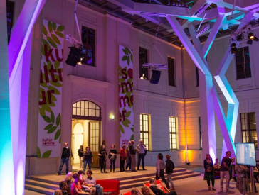 Festlich in Blau- und Lilatönen beleuchteter Innenhof des Altbaus des Jüdischen Museums Berlin bei Nacht. Im Hof sind viele Menschen, die stehen, sitzen oder flanieren