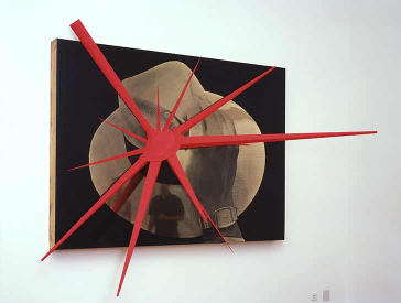 Das großflächige Kunstwerk zeigt einen stark vergrößertes Foto eines Hutes und einer Hand, die im Begriff ist, den Hut zu heben. Auf das Foto ist ein rotes dreidimensionales virusartiges Objekt montiert