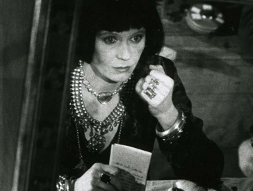 Film still in black and white: A woman with a lot of jewelry looks into a mirror.