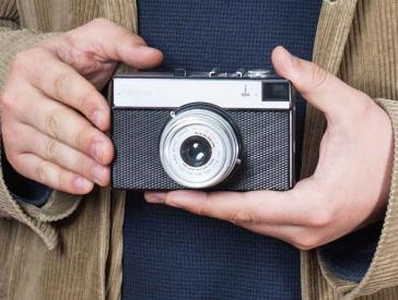 Zwei Hände halten einen analoge Kamera aus den 1980er Jahren