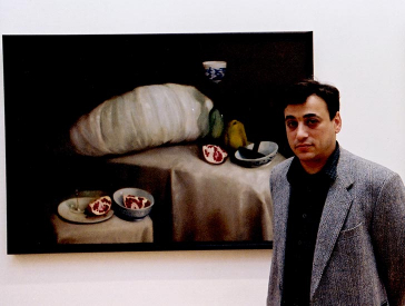 A young man stands in front of a still life depicting sliced pomegranates