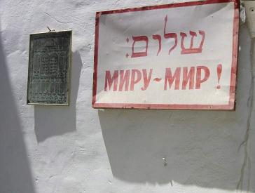 Hauswand mit einem Schild, auf dem in hebräischen Buchstaben Shalom und auf Russisch Friede für die Welt steht