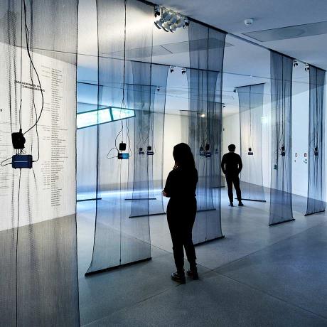 Ausstellungsansicht mit Besucher:innen, von der Decke hängen schwarze durchsichtige Stoffbahnen, daran befestigt sind Smartphones mit Klangwellen