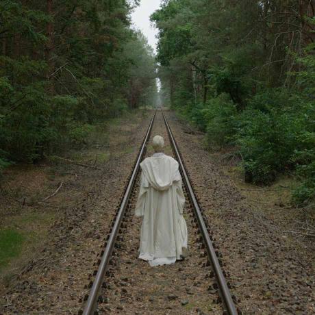 Das Bild zeigt eine Person von hinten, die mit einer weißen Kutte bekleidete ist. Die Person folgt Eisenbahnschienen, die schnurgerade durch einen Wald führen