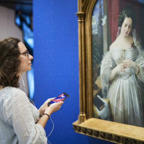 Young woman stands with smartphone and headphones in front of the portrait of Albertine Heine dressed as the bride of August Theodor Kaselowsky