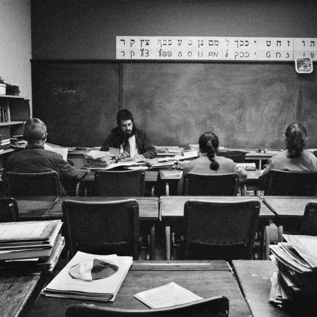 Schwarz-Weiß-Fotographie von einem Klassenraum, Rückenansicht von zwei Schülerinnen und einem Schüler, vor ihnen sitzt ein Lehrer, über der Tafel das hebräische Alphabet