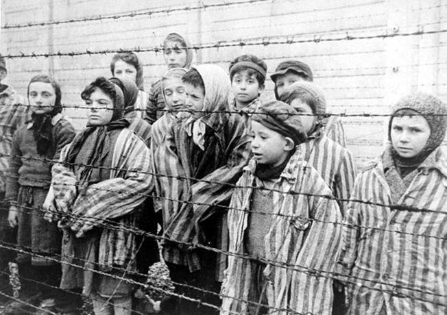 Schwarz-weiß Fotografie mit Kindern in Kleidung der Konzentrationslager in Auschwitz hinter einem Stacheldrahtzaun stehend