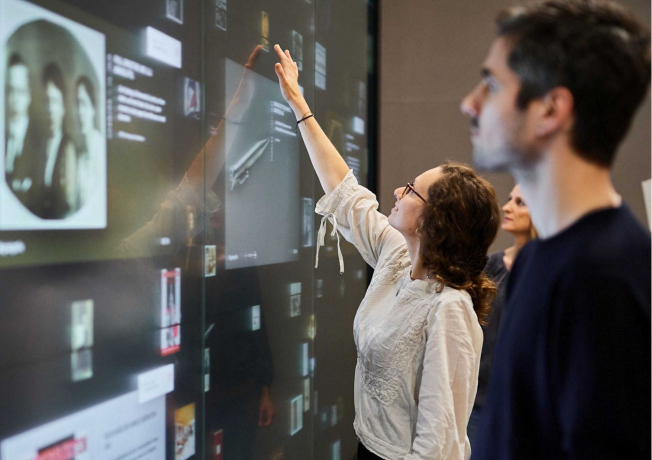 People touch a large touchscreen wall that displays documents and objects