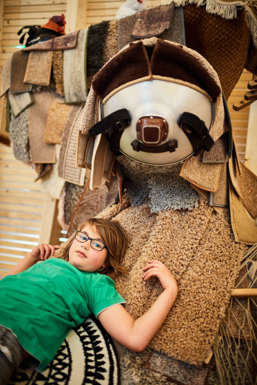 Boy lies on a sloth made of carpets and looks into the camera