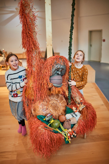 Two children stand next to an orangutan made of everyday objects