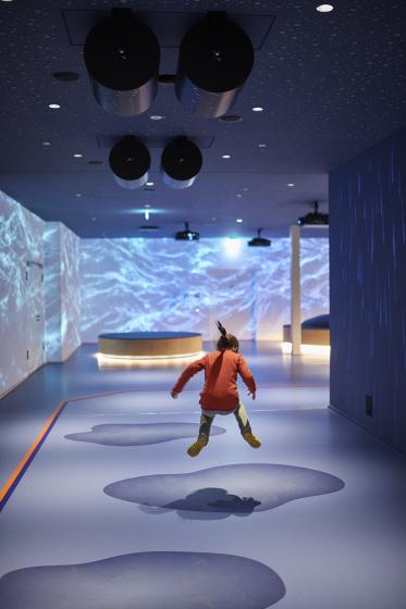 Kind springt in die künstlichen Pfützen der Kinderwelt Anoha