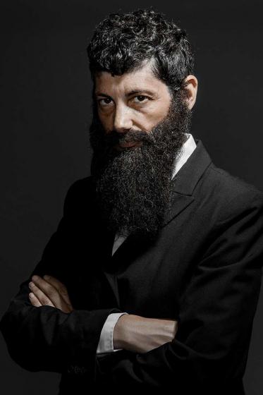 Brustbild eines bärtigen Mannes mit langem, dunklem Vollbart und dunklem Haar. Er trägt einen Anzug und verschränkt die Arme vor der Brust. Die linke Körperhälfte ist dem*der Betrachter*in zugewandt, das Gesicht ist im Halbprofil zu sehen.