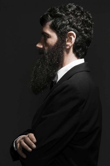 Brustbild eines bärtigen Mannes mit langem, dunklem Vollbart und dunklem Haar im Profil. Er trägt einen Anzug und verschränkt die Arme vor der Brust. Die linke Körperhälfte ist dem*der Betrachter*in zugewandt.