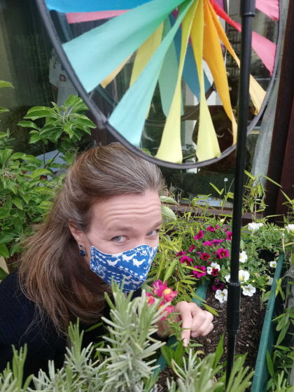 Selfie by Mirjam Bitter with a blue mask, standing on her balcony surrounded by plants - in the foreground a rainbow coloured mill.