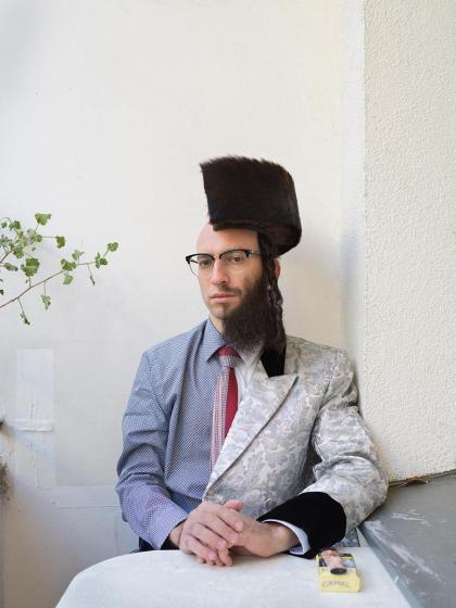 Fotografie eines Mannes, der entlang der Längsachse gleichsam in zwei Hälften geteilt ist: Auf der linken Seite trägt er Hemd und Glatze, auf der rechten Vollbart und einen (halbierten) Schtreimel auf dem Kopf