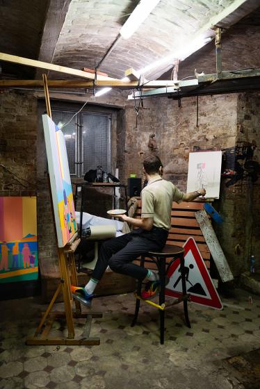 Fotografie einer Person vor einer Staffelei in einem Kellerraum, im Hintergrund steht ein Baustellenschild auf dem Boden