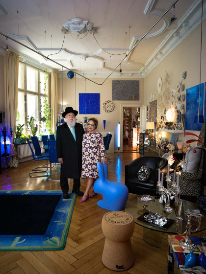 A couple, he in black suit with hat and white beard, she in floral dress with turquoise glasses, pose in a large, very colorfully decorated room, in front of them a blue bunny sculpture