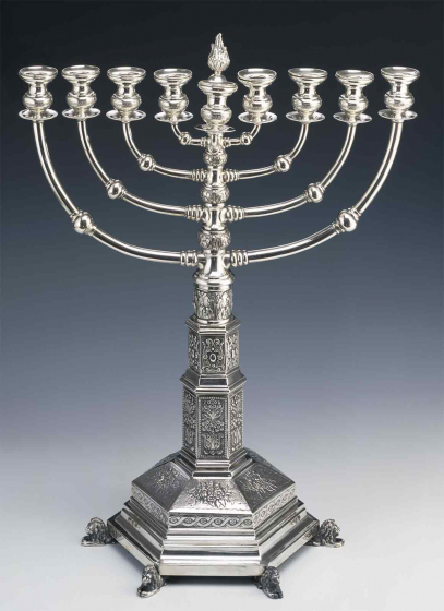 With its eight branches pointing in two directions, this silver Hanukkah menorah is an imitation of the original menorah in the Temple of Jerusalem. The richly ornamented base is held up by six lions.