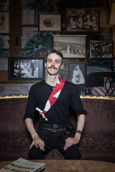 Ein junger Mann sitz in einem Raum der Ausstellung »Welcome to Jerusalem« im Jüdischen Museum Berlin