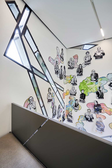 View from a staircase on a wall with cartoon-like busts of famous people