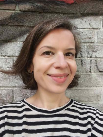 Selfie von Monika Flores vor einer Backsteinwand, die mit Graffitis besprüht ist.