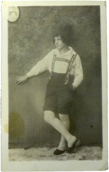 Studio portrait of an unknown woman in full-length figure with slippers, light pantyhose, light shirt, dark trousers with decorated suspenders and dark hat