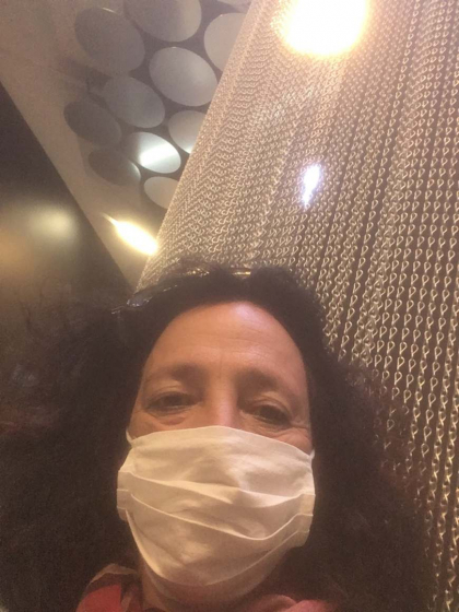 Porträt von Miriam Goldmann mit Mundschutz vor einem Kettenvorhand in den Räumen der Dauerausstellung
