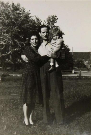 Schwarz-weiße Außenaufnahme einer Familie, der Vater trägt die einjährige Tochter auf dem Arm