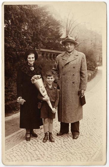 Foto von Familie Zwilsky im Monbijou-Park: Die Eltern haben Mäntel und Hüte auf. Klaus Zwilsky trägt ein Hemd und kurze Hosen und hat eine Schultüte in der Hand.