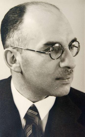 Schwarz-weiß-Porträt eines Mannes mit Brille, Schnauzer und hoher Stirn