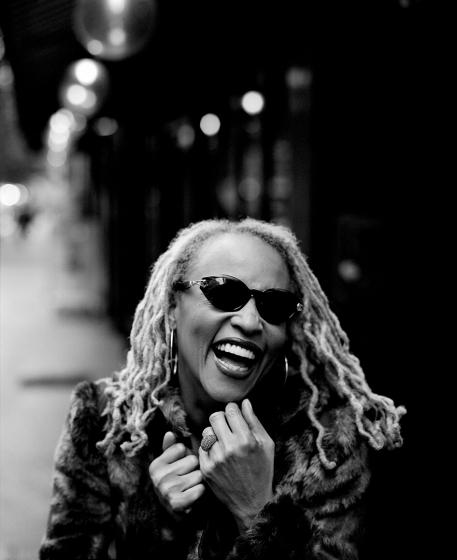 Cassandra Wilson mit Sonnenbrille und Pelzmantel lachend auf einer Straße.