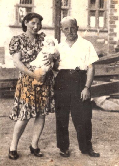 Black and white photo of a woman holding an infant and standing beside a man
