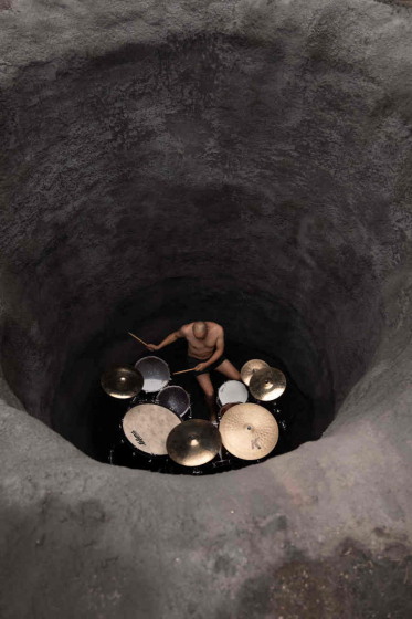 Man plays on a drum set in a hole in the ground