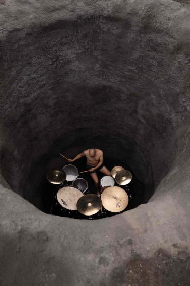 Mann spielt in einem Erdloch auf einem Schlagzeug