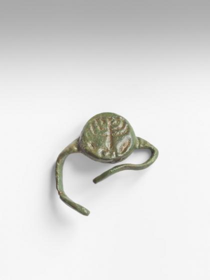 Grün angelaufener Ring mit Gravur, der in der Mitte offen ist