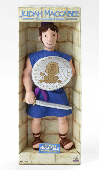 A Judah the Maccabee doll in its original sales packaging. The figure is smiling, dressed in a sleeveless knee-length blue tunic and Roman sandals, and holds a sword and a shield emblazoned with a lion and a Star of David
