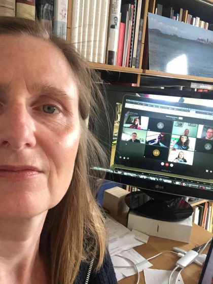Selfie by Henriette Kolb, standing with her back to her screen on which a video call is open.