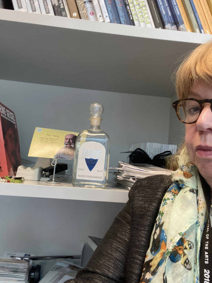 Selfie Cilly Kugelmann in front of a shelf with a vodka bottle and a postcard.